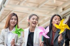 Młoda kobieta bawić się z papierowymi wiatraczkami lub silnika wiatrowego papierem Zdjęcie Stock