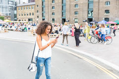 Młoda kobieta bawić się z zwiększającą rzeczywistości grze w Londyn Zdjęcie Royalty Free