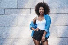 Młoda kobieta bezpłatny styl na ulicie na szarość izoluje posin zdjęcia stock