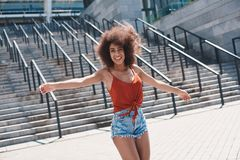 Młoda kobieta bezpłatny styl na ulicznych chodzących pobliskich schodkach wręcza a zdjęcie stock