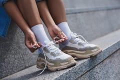 Młoda kobieta bezpłatny styl na ulicznym obsiadaniu na schodkach wiąże sho zdjęcie stock