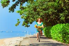 Młoda kobieta bicycling nabrzeże drogą wzdłuż tropikalnej morze plaży zdjęcie royalty free