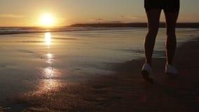 Młoda kobieta bieg na plaży blisko oceanu przy zmierzchu glidecam zbiory