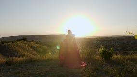 Młoda kobieta bieg w długiej purpurze ubierają przez winnicy na górze zbiory