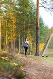 Młoda kobieta bieg w jesieni lasowy zmierzch zaświeca Obrazy Royalty Free