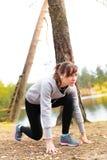 Młoda kobieta bieg w jesieni lasowy zmierzch zaświeca Zdjęcia Royalty Free