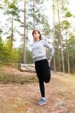Młoda kobieta bieg w jesieni lasowy zmierzch zaświeca Zdjęcie Royalty Free