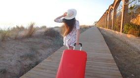Młoda kobieta bieg z czerwoną walizką zbiory wideo