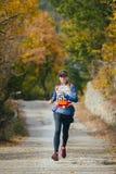 Młoda kobieta biega przez drogę w jesień lesie Zdjęcia Stock