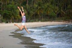 Młoda kobieta biega skoki w morze na tropikalnej plaży Szczęśliwy obrazy royalty free