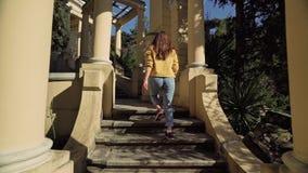 Młoda kobieta biega w górę kamiennych schodków z antykwarskimi kolumnami w pięknym parku zbiory