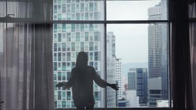 Młoda kobieta biega zasłony na dużym okno out i otwiera i przyglądający jej mieszkanie na miasto budynkach swobodny ruch zbiory wideo