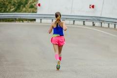 Młoda kobieta biegacz biega na halnej drodze w jaskrawych różowych uciskowych skarpetach fotografia stock