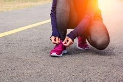 Młoda kobieta biegacz wiąże shoelaces Obrazy Stock