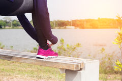 Młoda kobieta biegacz wiąże shoelaces fotografia royalty free