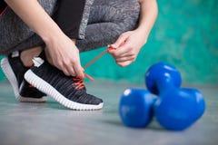 Młoda kobieta biegacz wiąże shoelaces dieta około tło bow puste pojęcia wyświetlania numerów jego skali diety środki wiążące taśm Zdjęcia Royalty Free