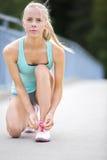 Młoda kobieta biegacz wiąże shoelaces na moscie Zdjęcia Stock