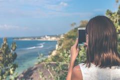 Młoda kobieta bierze fotografie na falezie z pięknym oceanu tłem przy słonecznym dniem Bali wyspa zdjęcie royalty free