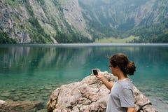 Młoda kobieta bierze fotografie przy pięknym i mglistym jeziorem obraz stock