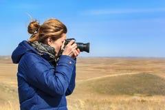 Młoda kobieta bierze obrazki przy kamerą na niebieskiego nieba tle fotografia royalty free