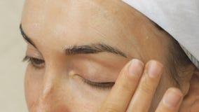 Młoda kobieta bierze opiekę jej twarzy skóra w domu zbiory wideo