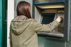 Młoda kobieta bierze pieniądze od ATM Chwyta kartę od ATM Finanse, kredytowa karta, wycofanie pieniądze Obrazy Stock