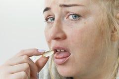Młoda kobieta bierze pigułki, leka, zdrowie lub medycyny pojęcia, zdjęcia stock
