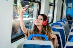 Młoda kobieta bierze selfie na pociągu z jej telefonem zdjęcie stock
