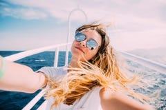 Młoda kobieta bierze selfie t na jachcie unosi się w morzu Fotografia Stock
