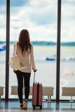 Młoda kobieta blisko okno w lotniskowym holu czekaniu dla przyjeżdża Obrazy Stock