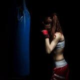 Młoda kobieta boks na uderza pięścią torbie obrazy stock