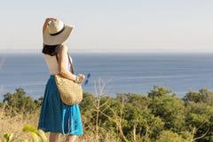 Młoda kobieta & x28; brunette& x29; w błękitnej spódnicy i kapeluszu spojrzeniach przy morzem Obraz Stock