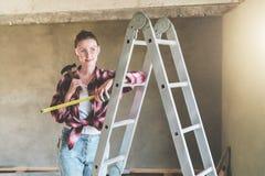 Młoda kobieta budowniczy, ubierający w szkockiej kraty koszula i budów szkłach, stojaki w warsztacie na stepladder Zdjęcia Royalty Free