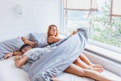 Młoda kobieta budził się up w łóżkowym gniewnym przyczyna mężczyzna wziąć prześcieradło obraz stock