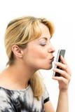 Młoda kobieta całuje jej telefon komórkowego Obraz Royalty Free