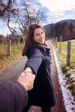 Młoda kobieta chodzi outdoors i trzyma rękę mężczyzna zdjęcia stock