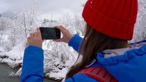 Młoda kobieta chodzi przez most przez rzekę i używa smartphone dla robi fotografiom piękny zima śnieg zbiory wideo