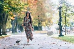 Młoda kobieta chodzi w jesień parku z małym szczeniakiem w okularach przeciwsłonecznych Plenerowy stylu życia portret dosyć uśmie obraz stock