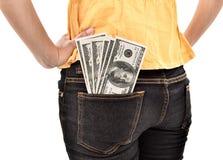 Młoda kobieta chuje dolary w kieszeniowym pieniądze Obrazy Stock