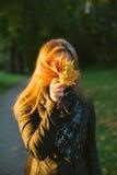 Młoda kobieta chuje twarz za wiązką liście zdjęcie stock