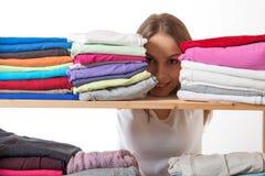 Młoda kobieta chuje za półką z odzieżą zdjęcie stock