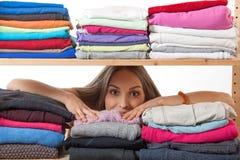 Młoda kobieta chuje za półką z odzieżą obrazy stock