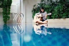Młoda kobieta chwyta gitary klasyk w jej obsiadaniu obok p i ręce obrazy stock