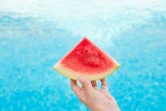 Młoda Kobieta chwyty w ręka klinu plasterku Soczysty arbuz Pływackim basenem błękitna woda sunlight Urlopowy relaks fotografia royalty free