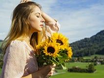Młoda kobieta cieszy się światła słonecznego mienia słoneczniki fotografia stock