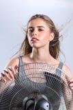 Młoda kobieta cieszy się chłodno wiatr od elektrycznego fan zdjęcie royalty free
