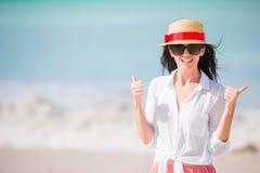 Młoda kobieta cieszy się słońce sunbathing perfect turkusowym oceanem Dziewczyna podnosi aprobaty outdoors Obrazy Stock