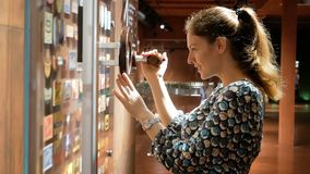 Młoda kobieta considering ławkę z ikonami przez powiększać - szkło który rusza się Ciekawość przy pracą Piwny muzeum zdjęcie wideo