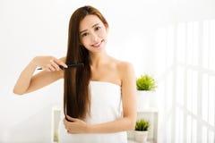 Młoda kobieta czesze jej włosy w żywym pokoju zdjęcie stock