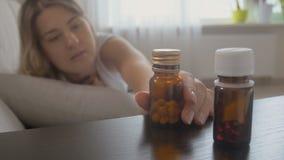 Młoda kobieta czuciowy chory bierze zbiornik z medycynami od wezgłowie stołu zbiory